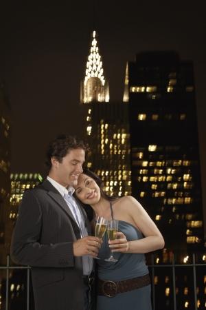 couple lit: El tostar con Champ�n contra Nueva York horizonte de la noche