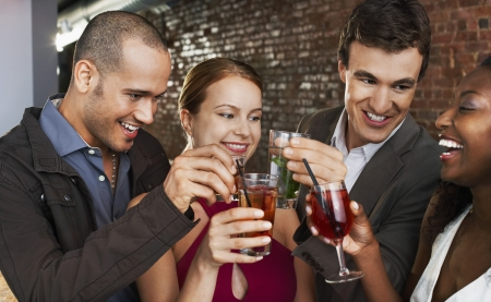 racially diverse: Couples Toasting at Bar