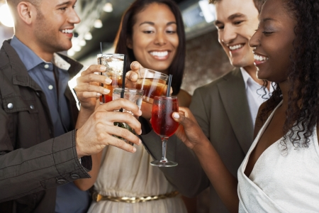 racially diverse: Friends Toasting at Bar
