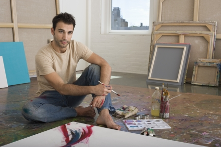 25 to 30 year olds: Artist Working on Canvas on Floor of Studio