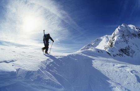 pinnacle: Skier hiking to mountain summit