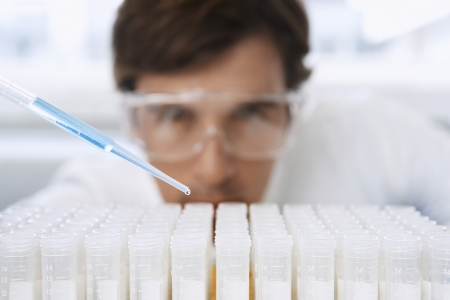 laboratory technician: Lab Worker Adding Liquid to Test Tubes LANG_EVOIMAGES