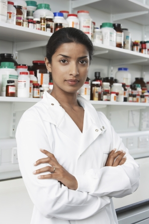 pharmacy technician: Female lab worker standing pill bottles behind LANG_EVOIMAGES