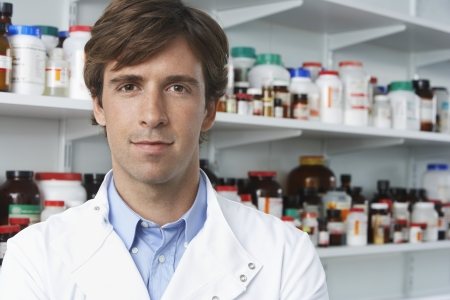 pharmacy technician: Male lab worker standing pill bottles behind LANG_EVOIMAGES