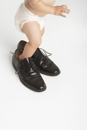 wingtips: Baby Standing in Mans Shoes