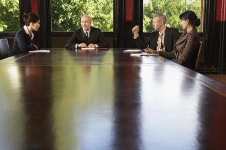 Boardroom meeting: Businesspeople meeting around boardroom table LANG_EVOIMAGES
