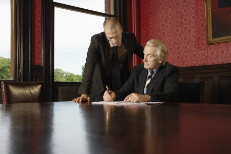 dictating: Two Men in Conference Room one leaning over other
