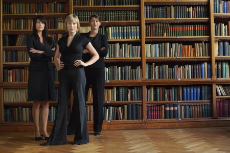 law suit: Three lawyers in library standing LANG_EVOIMAGES