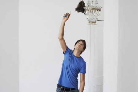 dusting: Man dusting crystal chandelier in home