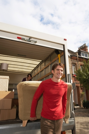 removals: Moving Couple Carrying Sofa LANG_EVOIMAGES