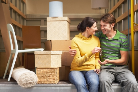 moving out: Couple Sitting in Back of Moving Van handing over keys
