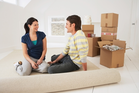 Couple sitting on half-rolled carpet in new home Stock Photo - 19326860