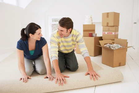 Couple unrolling carpet in new home Stock Photo - 19213785