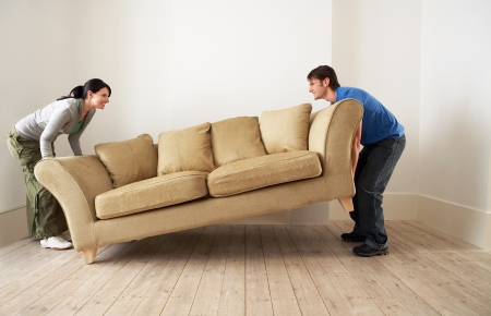 Couple lifting sofa in empty room Stock Photo - 19326889