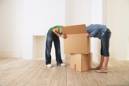 Junges Paar Auspacken Feld in neues Zuhause mit Gesichtern versteckt