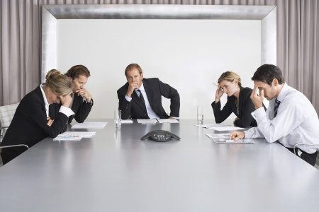 teleconferencing: Frustrated Businesspeople Listening to Conference Call