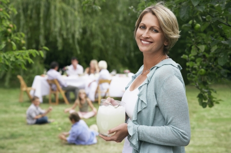 one person with others: Woman Holding Lemonade at Family Picnic LANG_EVOIMAGES