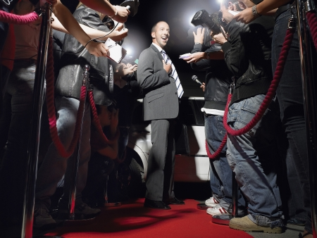 red carpet event: Man on red carpet in front of paparazzi