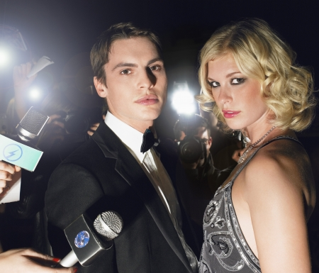 Couple posing in front of paparazzi Stock Photo
