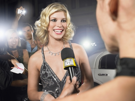 one person with others: Glamourous Woman Giving Red Carpet Interview
