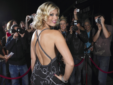 carpet: Woman posing on red carpet in front of fans
