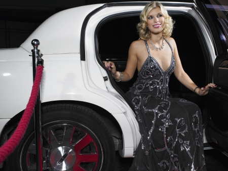 'evening wear': Woman in evening wear getting out of limousine