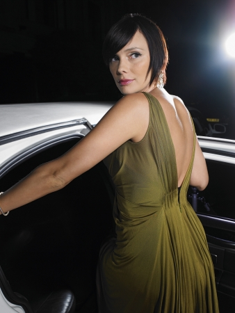 evening wear: Woman in evening wear getting into limousine LANG_EVOIMAGES