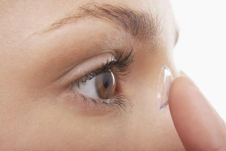 lentes de contacto: Mujer joven que pone en la lente de contacto