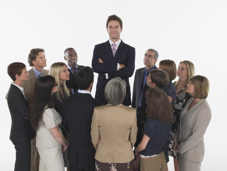 late 40s: Group of Businesspeople Staring at Tall Man