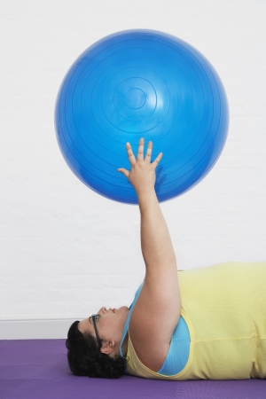 exerting: Overweight Woman Holding Exercise Ball