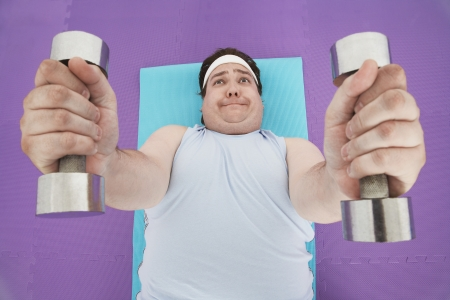 free weight: Overweight Man Lifting Weights