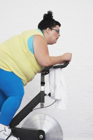 wellness sleepy: Overweight Woman Riding Exercise Bike LANG_EVOIMAGES