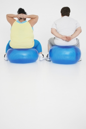 exerting: Overweight Couple Exercising on Balls
