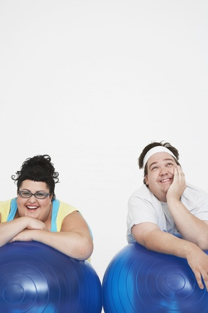 man only: Overweight Couple Resting on Exercise Balls