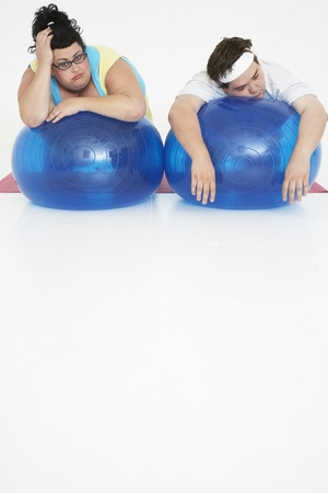 exerting: Overweight Man and Woman with Exercise Balls