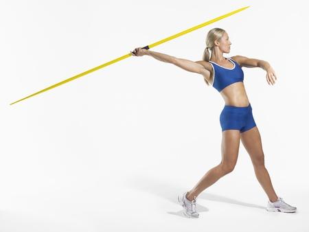 exerting: Female Athlete Throwing Javelin LANG_EVOIMAGES