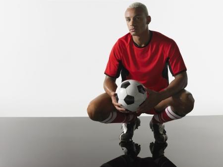 en cuclillas: Hombre sosteniendo la pelota de f�tbol
