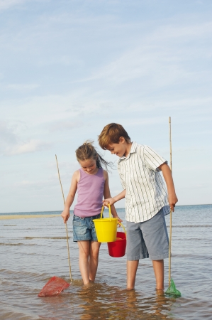 Brother and Sister Playing on Beach Imagens