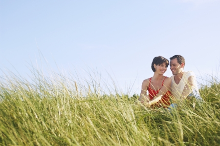late thirties: Couple Sitting in Tall Grass