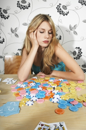 tedious: Woman Sitting at Table with Chips and Playing Cards LANG_EVOIMAGES