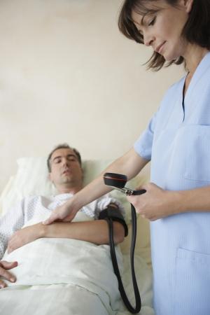 signos vitales: La enfermera toma la presión arterial del paciente y pulso
