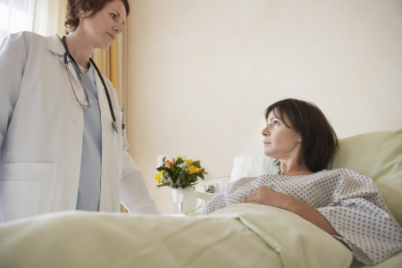 maladies: Doctor With Patient in Hospital Bed