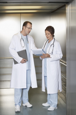 Physicians Discussing Chart in Elevator Stock Photo - 18896882