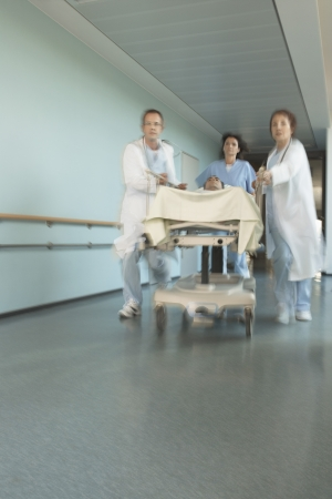 healthcare facilities: Physicians Rushing Patient Down Corridor LANG_EVOIMAGES