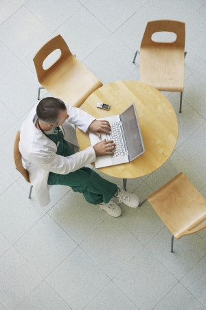 late forties: Physician Using Laptop During Break LANG_EVOIMAGES