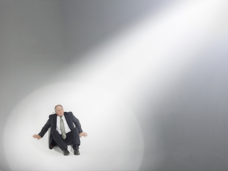anguished: Businessman sitting looking up at source of spotlight LANG_EVOIMAGES
