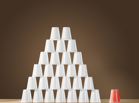 nonconformity: Pyramid of white plastic cups on table next to single red cup