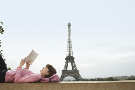 weekend break: France Paris Young woman reading book on balcony in front of Eiffel Tower LANG_EVOIMAGES