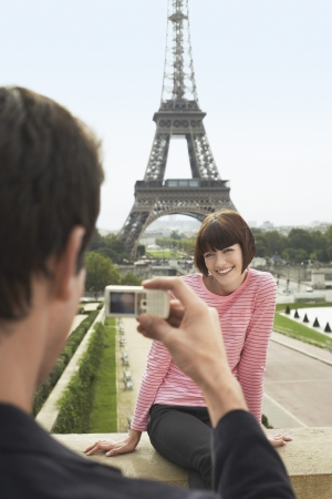 holiday maker: France Paris Man photographing woman in front of Eiffel Tower