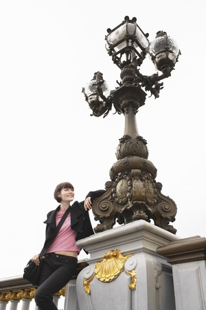weekend break: Young woman leaning on ornate streetlight LANG_EVOIMAGES